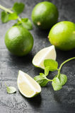 Fresh lime and mint on the black table. Selective focus Stock Images