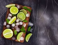 Fresh lime, mint and ice on cutting board. Ingredients for Mojito. Fresh lime, mint and ice on cutting board on dark background. Ingredients for Mojito or royalty free stock photos