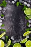 Fresh lime, mint and ice on dark background. Ingredients for Mojito or Cocktail. Top view royalty free stock photo