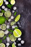 Fresh lime, mint and ice on dark background. Ingredients for Mojito or Cocktail. Top view stock image