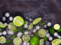 Fresh lime, mint and ice on dark background. Ingredients for Mojito or Cocktail. Top view stock photography