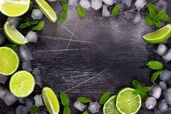 Fresh lime, mint and ice on dark background. Ingredients for Mojito or Cocktail. Top view royalty free stock image