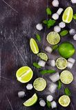Fresh lime, mint and ice on dark background. Ingredients for Mojito or Cocktail. Top view royalty free stock photography