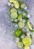 Fresh lime, mint and ice on grey background. Ingredients for Mojito or Cocktail. Top view royalty free stock images
