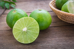 Fresh lime with slices on wooden table Royalty Free Stock Photos
