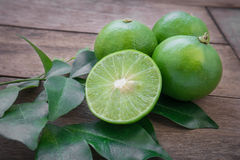 Fresh lime with slices on wooden table Royalty Free Stock Images