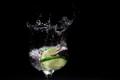 Fresh lime splashing into glass of liquid Stock Photos