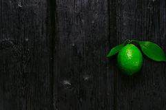 Fresh lime on the wooden background charred Stock Photography