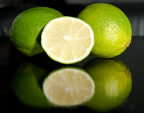 Fresh limes. 2 whole limes and a section of a third one on a black table Stock Image