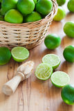 Fresh limes. In basket and squeezer, selective focus Stock Photography