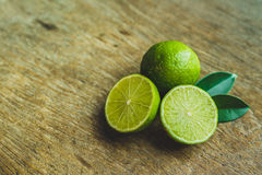 Fresh limes. In a bowl with leaves cut in half on wooden table, Top view, background Royalty Free Stock Photography