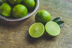 Fresh limes. In a bowl with leaves cut in half on wooden table, Top view, background Stock Photos
