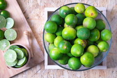 Fresh limes in bowl on wooden table Stock Photo