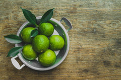Fresh limes. Cut in half with leaves in a bowl on wooden table, Top view, background Royalty Free Stock Photo