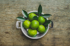 Fresh limes. Cut in half with leaves in a bowl on wooden table, Top view, background Royalty Free Stock Photos