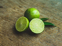 Fresh limes. Cut in half with leaves  on wooden table,  background Royalty Free Stock Photography