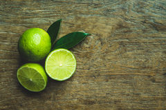 Fresh limes. Cut in half with leaves on wooden table, Top view, background Royalty Free Stock Images