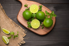 Fresh limes on cutting board on wooden table. Top view, backgrou Stock Images