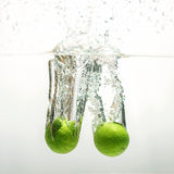 Fresh limes. Fresh limes falling into water Stock Photo