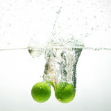 Fresh limes. Fresh limes falling into water Royalty Free Stock Photo