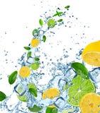 Fresh limes and lemons in water splash. Stock Images