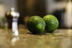 Fresh limes on a marble countertop Royalty Free Stock Photos