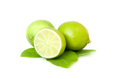 Fresh limes over white background. Two whole limes, one half lime, with leaves, isolated on white Stock Photo