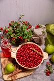 Lingonberries and lingonberry products. Fresh lingonberries, lingonberry drink, jam, cinnamon and pears on the table. Healthy food. Lingonberry, vertical, rustic stock photo