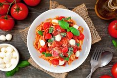 Linguine pasta with tomatoes, mozzarella and basil, above view table scene over wood. Fresh linguine pasta with tomatoes, mozzarella cheese and basil. Above view stock photo