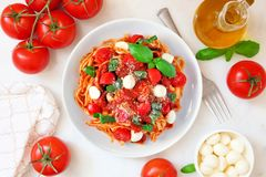 Linguine pasta with tomatoes, mozzarella and basil, above view table scene over white marble. Fresh linguine pasta with tomatoes, mozzarella cheese and basil royalty free stock photos