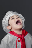 Fresh, little boy preparing healthy food on kitchen over grey ba Stock Photo