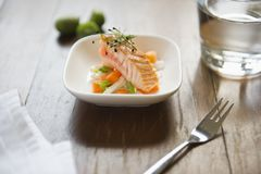 Fresh little salad with salmon and sprouts. On wooden table with glass of water, little fork, napkin and some green citrus fruits Royalty Free Stock Photos