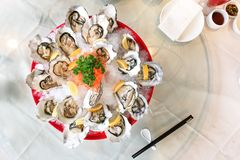Fresh live raw oyster served with lemon and chili sauce. In restaurant Stock Image