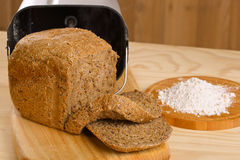 Fresh loaf of rye bread and some flour on wooden. Fresh loaf of rye bread with breadmaker and gluten free flour on wooden table royalty free stock photography