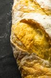 Loaf of white wheat bread. Fresh loaf of white wheat bread on black background royalty free stock photography