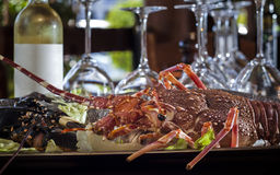 Fresh lobster and bottle of white wine. On table in restaurant Stock Photography