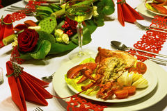 Fresh lobster on festive table. Fresh lobster and white wine on a festive table with red folded napkins Royalty Free Stock Image