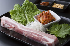 Fresh loin pork with lettuce and kimchi on black dish. Deliciously Stock Photography