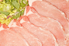 Fresh Loin Steaks. Fresh raw pork loin steaks background with salad Royalty Free Stock Images