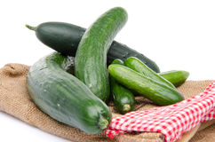 Fresh long and mini cucumbers on burlap Stock Images