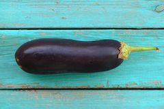 Fresh long purple aubergine on blue table Royalty Free Stock Photo