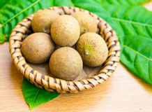 Fresh longan with longan leaf set on wooden table Royalty Free Stock Images