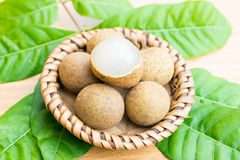 Fresh longan with longan leaf set on wooden table Stock Photo