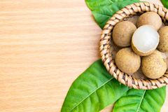 Fresh longan with longan leaf set on wooden table Royalty Free Stock Photo