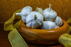 Garlic in hand turned hardwood bowl on a cork wood background. Royalty Free Stock Photos