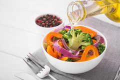 Fresh low-calorie salad with broccoli, pepper and onion. Pour olive oil into bowl. Diet organic food Stock Images