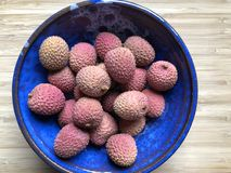 Fresh lychees in a blue ceramic bowl stock image