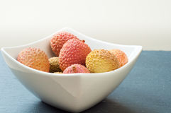 Fresh lychees. Bowl of fresh ripe lychees on a gray slate table top Royalty Free Stock Images