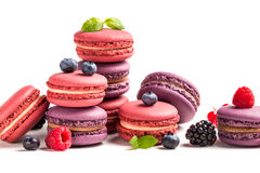 Fresh macaroons with berry fruits on white background Royalty Free Stock Photo