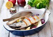 Fresh mackerel fish baked with a lemon, bow, salt and pepper on a wooden table Royalty Free Stock Photography